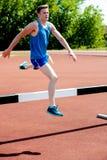 男性运动员跳跃的障碍 免版税库存图片