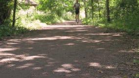 男性运动员,主角一种健康生活方式 他在公园跑在一个夏日 股票视频