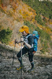 男性运动员去山在他后一个小孩子 免版税库存图片