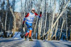 年轻男性运动员滑雪者在乘坐冬天森林经典的样式赛跑上升 图库摄影