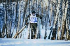 年轻男性运动员滑雪者在乘坐冬天森林经典的样式赛跑上升 免版税图库摄影