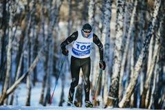男性运动员滑雪者在乘坐冬天森林经典的样式赛跑上升 库存图片