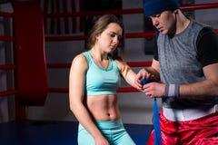 男性运动的拳击手绷带为运动女性做准备 图库摄影