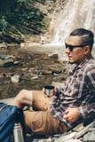 男性远足者休息和饮料茶或者咖啡从远足休闲假期旅行概念的热水瓶 库存图片