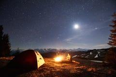 男性远足者充分有休息在他的阵营在森林附近在晚上在美丽的夜空下星和月亮 库存图片