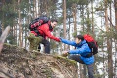 年轻男性远足者帮助的朋友,当迁徙在森林里时 库存照片