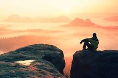 男性远足者背面图坐岩石峰顶,当享受在mounrains谷上时的五颜六色的破晓 免版税图库摄影