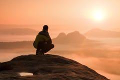 男性远足者背面图坐岩石峰顶,当享受在mounrains谷上时的五颜六色的破晓 库存图片