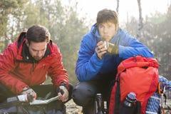 男性远足者读书地图,当朋友食用咖啡在森林时 库存照片