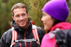 男性远足者画象在森林里谈话与妇女 免版税图库摄影