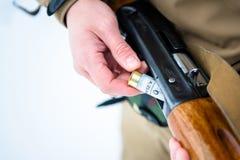 男性递猎人在backg的被插入的弹药筒12口径步枪 免版税库存图片