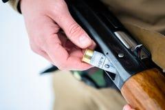 男性递猎人在backg的被插入的弹药筒12口径步枪 免版税库存照片