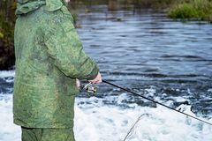 男性钓鱼者在快速的水中风行一个转动的卷轴鱼在淡季 库存图片