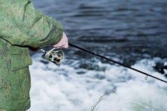男性钓鱼者在快速的水中风行一个转动的卷轴鱼在淡季 免版税库存照片