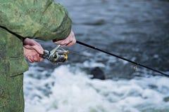 男性钓鱼者在快速的水中风行一个转动的卷轴鱼在淡季 图库摄影