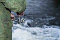 男性钓鱼者在快速的水中风行一个转动的卷轴鱼在淡季 免版税库存图片