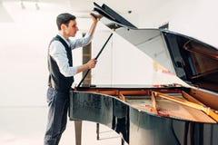 男性钢琴演奏家打开黑大平台钢琴盒盖  库存图片