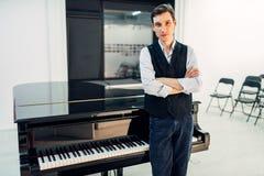 男性钢琴演奏家站立在黑大平台钢琴 免版税库存图片
