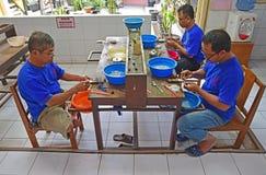 男性银器匠洗涤物,清洗和投入最后的接触的一个小组在纯净的银色装饰品 免版税图库摄影