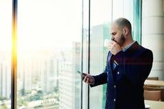 男性银行家是与拷贝空间的常设近的办公室窗口背景您的广告的 库存图片