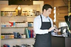 男性销售画象辅助在美容品商店 免版税库存图片