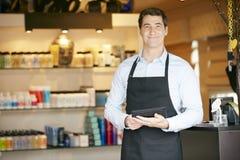 男性销售画象辅助在美容品商店 图库摄影