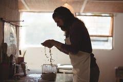 男性陶瓷工洗涤的手在工作在瓦器轮子以后 免版税库存图片