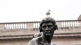 男性雕象与鸟的在他的头 免版税图库摄影