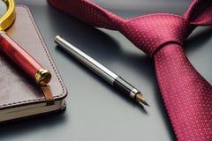 男性静物画 有笔记本的钢笔在领带说谎 免版税库存图片