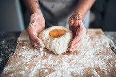 男性面包师手与鸡蛋混合面团 免版税库存图片