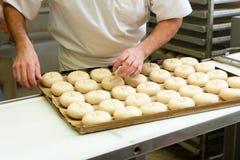男性面包师烘烤小圆面包 图库摄影