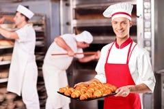 男性面包师藏品新月形面包在面包店 免版税库存图片