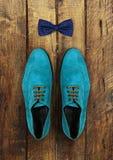 男性鞋子和弓领带在木的褐色 免版税库存图片