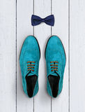 男性鞋子和弓领带在白色木背景 免版税库存图片