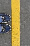男性鞋子顶视图在柏油路的有黄线的, Ste 免版税库存图片