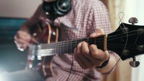 男性音乐家组成并且记录弹奏在手上的吉他使用计算机,焦点和仪器的电影配乐 股票录像