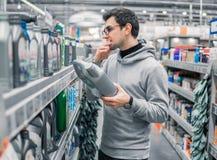 男性顾客买的引擎润滑油在汽车超级市场 免版税图库摄影