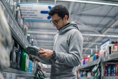 男性顾客买的引擎润滑油在汽车超级市场 库存图片