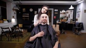 男性顾客参观的理发店和女性理发师 供以人员看他自己在镜子在完成的工作-他的 股票录像