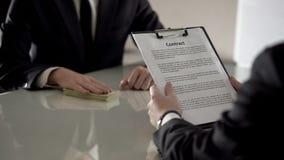 男性顾客读书放款合同,拿着金钱,抵押的银行雇员 库存图片