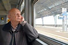 男性领抚恤金者周道地看在电车外面 免版税图库摄影