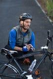 男性骑自行车的人在握他的受伤的腿的痛苦中 免版税库存照片