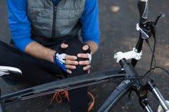 男性骑自行车的人的中央部位在握他的受伤的腿的痛苦中 免版税库存图片