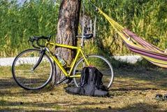 男性骑自行车者、吊床、休息、日出和湖或者河背景 库存照片