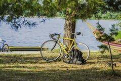 男性骑自行车者、吊床、休息、日出和湖或者河背景 免版税库存照片