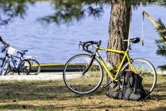男性骑自行车者、吊床、休息、日出和湖或者河背景 免版税库存图片