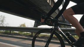 男性骑自行车者骑马自行车和改变的齿轮 在背景的太阳发光和桥梁 紧密探究射击 r ? 股票视频