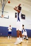 男性高中蓝球运动员射击惩罚 库存图片