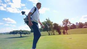 男性高尔夫球运动员在领域走,运载袋子用设备 高尔夫球场的高尔夫球运动员 股票录像