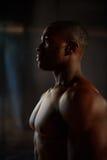男性黑非裔美国人的健身式样显示在演播室干涉有黑暗的背景 免版税库存照片